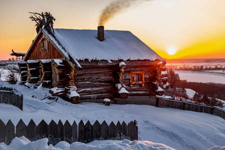 Forest cabin in winter with a wooden hut in the snow. Log house on the evening sky Foto de archivo