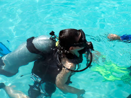 scuba mask: A boy taking scuba diving lessons in the caribbean resort.