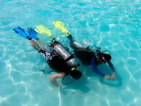 picada: Un chico tomando lecciones de buceo en el Caribe resort.