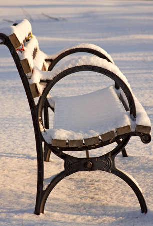 Snow covered park bench at early morning light. photo