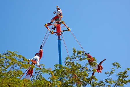 traje mexicano: TULUM, M?ICO - 2 de noviembre de 2010: India Maya artistas callejeros conocido como Flying mayas realizando acrobacias tradicionales mayas Cultural el 2 de noviembre de 2010 en Tulum, M?co por los mayas del sitio arqueol?o de las Ruinas. Editorial