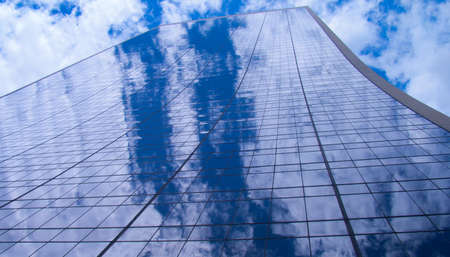 A photograph of the steel and glass skyscraper in New York City, dissolving into the sky above with clouds reflections.