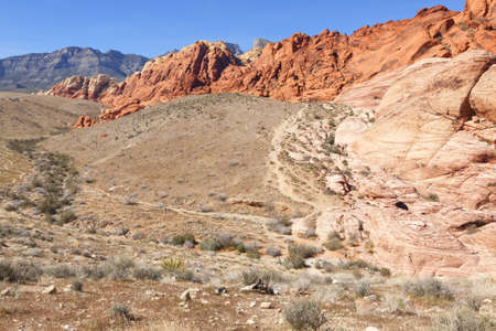 View of dry landscape and red rock formations of the Red Rock Canyon in the Mojave Desert. photo