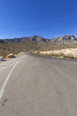 View of dry landscape and red rock formations of the Mojave Desert.. photo