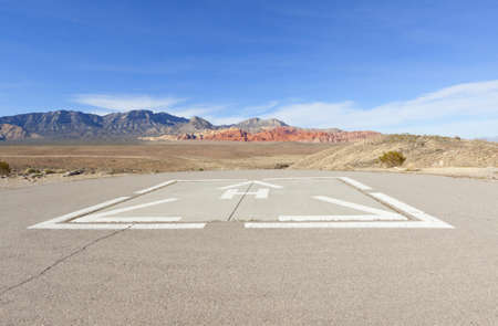 helicopter pad: Helicopter pad against the dry landscape and red rock formations of the Mojave Desert.