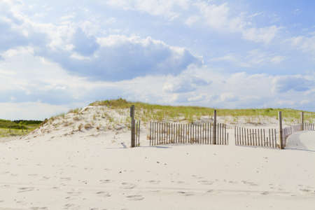 Sand dunes on Atlantic coast with a fence. photo