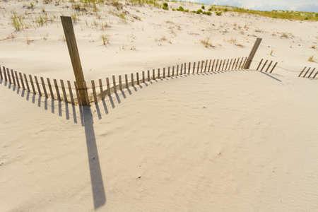 Sand dunes on Atlantic coast with a fence. photo