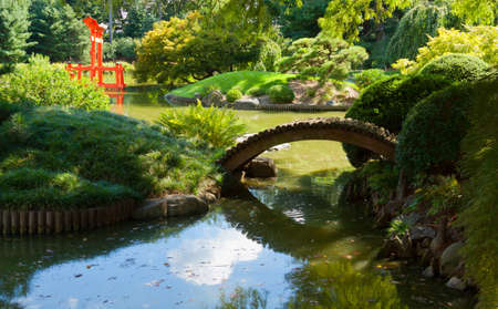 koi: Japanese Garden and pond with a red Zen Tower  Stock Photo