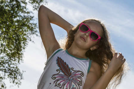 long nose: Young girl in sunglasses fixing her long blond hair in the sunlight on a hot afternoon. Stock Photo