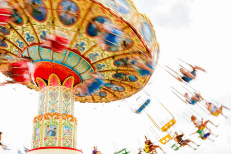 Children riding a colorful merry-go-round at the county fair. Reklamní fotografie - 42122193