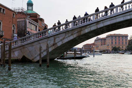 sited: Venice, Italy - April 1, 2013: Street views of canals and ancient architecture in Venice, Italy. Venice is a city in northeastern Italy sited on a group of 118 small islands separated by canals and linked by bridges.