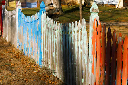 Colorful picket fence on a farmland. Stock Photo