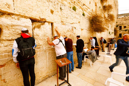 israeli: Jerusalem, Israel-March 14, 2017: Jews pray at The Western Wall - the holiest place where Jews are permitted to pray, though it is not the holiest site in the Jewish faith, which lies behind it, on Temple Mount. Editorial