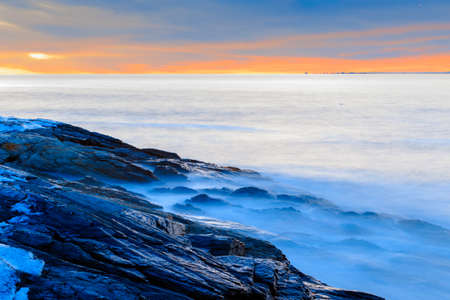 Beautiful sunset on a rocky ocean shore Imagens