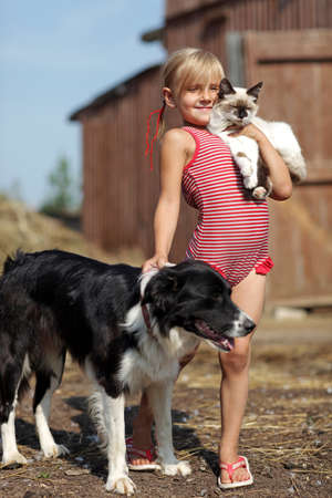 Plays a girl and with a cat and dog in nature photo