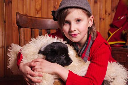sheepskin: Chica joven que abraza un cachorro envuelto en una piel de oveja Granja