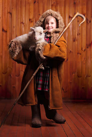 good shepherd: Playful girl shepherd with his staff under his arm a lamb on the farm Stock Photo