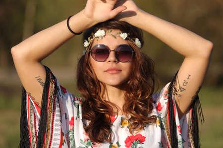 mujer hippie: Mujer joven en estilo hippie que mira la cámara y la celebración de las manos sobre la cabeza