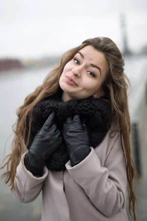 Beautiful girl in a natural make-up cute smiling at the camera. Girl in a black coat, a scarf and a red dress against a gray sky. Not Isolated. Autumn bank overcast