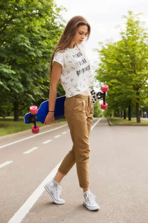 Young girl fashion model posing with longboard in the park on the track. Lifestyle outdoor portrait Stock Photo