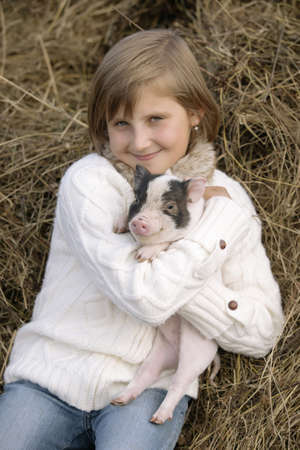 pigling: Young girl sitting on hay, smiling and holding a pig in his smiles. Outdoors. Lifestyle portrait Stock Photo