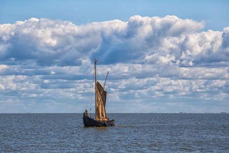 Retro wooden sailing ship sails into the sea. 写真素材