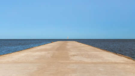 Road leading to the sea to the horizon. Sailboat on the horizon. 写真素材