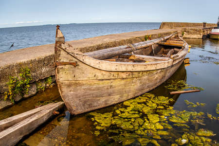 Old wooden boat stands near the pier.