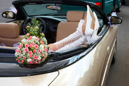 Bride in a cabriolet with wedding flowers. 写真素材