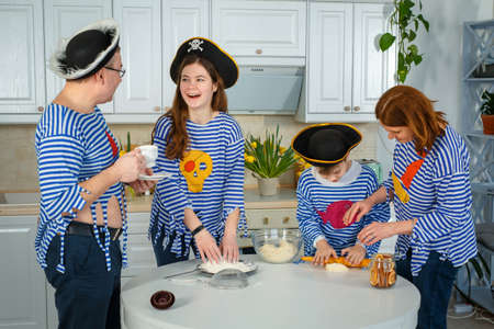 Photo session - friendly family. The family cooks together. Husband, wife and their children in the kitchen. Family kneads dough with flour. Prepare the dough in the kitchen.