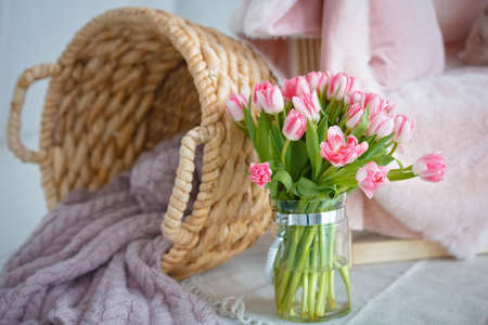 Delicate bouquet of pink tulips with a wicker basket.