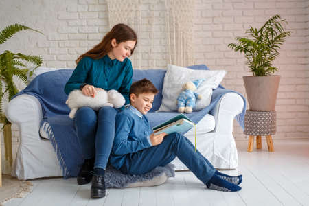 Photo session - friendly family. Brother and sister are reading a book. 写真素材