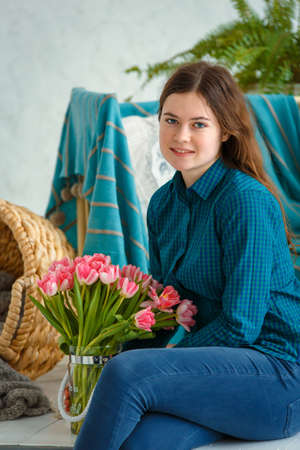 Photo session - friendly family. Spring portrait of a girl with pink tulips.