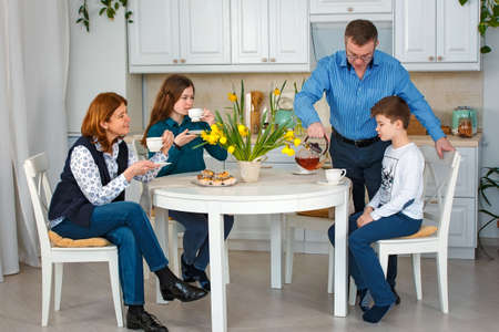 Photo session - friendly family. Morning tea. Father pours tea.