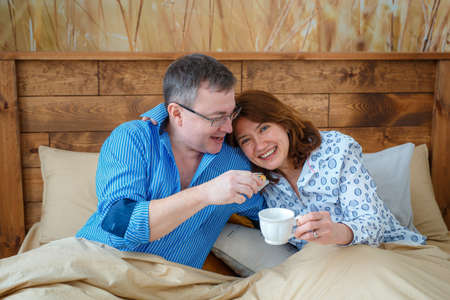 Photo session - friendly family. Morning tea. Husband brought his wife tea coffee to the bed. 写真素材