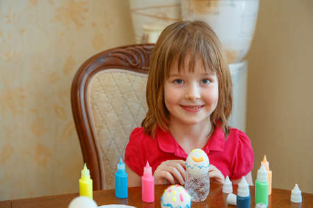 The girl is fun painting eggs for Easter. We paint eggs in bright colors. Happy easter 스톡 콘텐츠