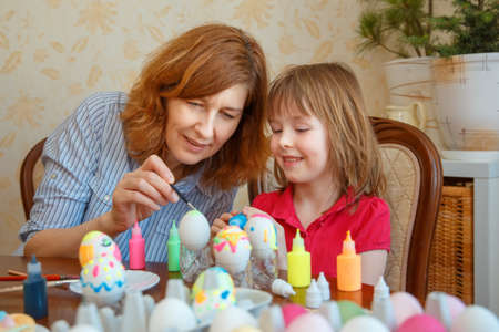 Mom and daughter have fun painting eggs for Easter. We paint eggs in bright colors.