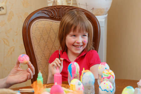 The girl is fun painting eggs for Easter. We paint eggs in bright colors. Happy easter 写真素材