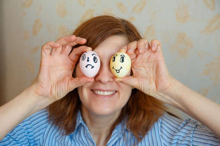 Girl shows painted eggs for Easter with funny faces. Happy easter