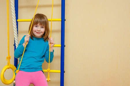 The girl cheerfully sits on a sports ladder. A girl sits on a swing.