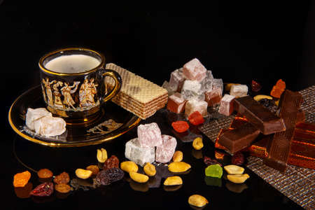 Natyutmort oriental sweets and a cup of hot coffee on a black background.