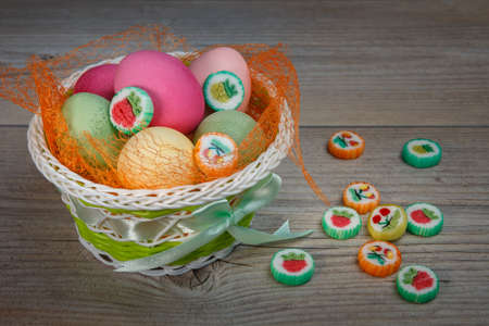 Multi-colored Easter eggs and sweets in a beautiful basket. Get ready for Easter.