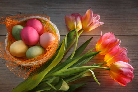 Multi-colored Easter eggs in a beautiful basket and a bouquet of tulips. Get ready for Easter.