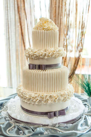 Big two-level anniversary wedding cake with flowers from pearl cream. 写真素材