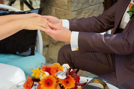 A man holds the hands of his bride. Bridal bouquet 写真素材