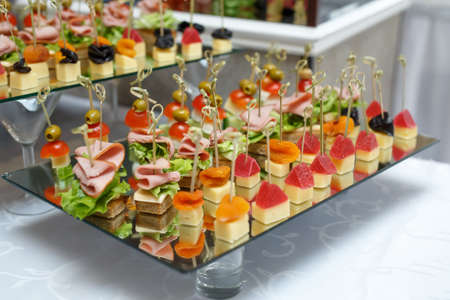 Delicious canapes with ham, cheese and fruit. Snacks 写真素材