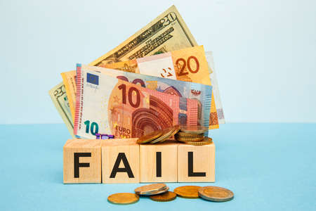 Fail word written on wood cubes on the background of various banknotes. Financial concept 스톡 콘텐츠