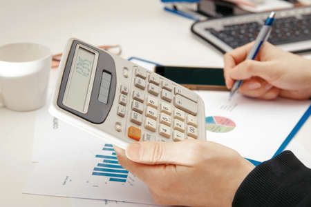 A young specialist works with financial documents at a computer.