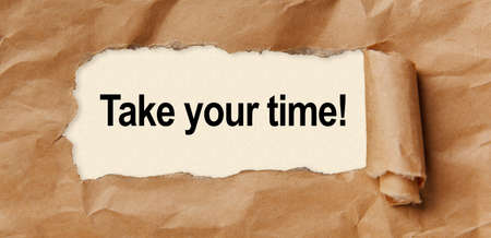 Text Take your time appearing behind torn brown paper 免版税图像