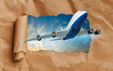 Airplane flying through torn paper. Travel and air transportation concept.